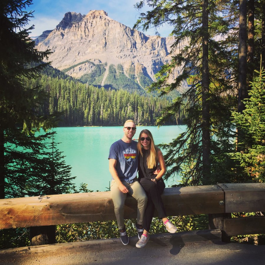 A man and woman sitting on a log fence side by side in front of an emerald coloured lake. There is a tall mountain rising in the distance, and they are framed by evergreen trees.