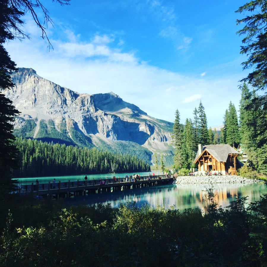 A view of an emerald coloured lake with a wooden cabin in the distance right, and mountains rising to the left. It is framed by evergreen trees and a bright blue sky.