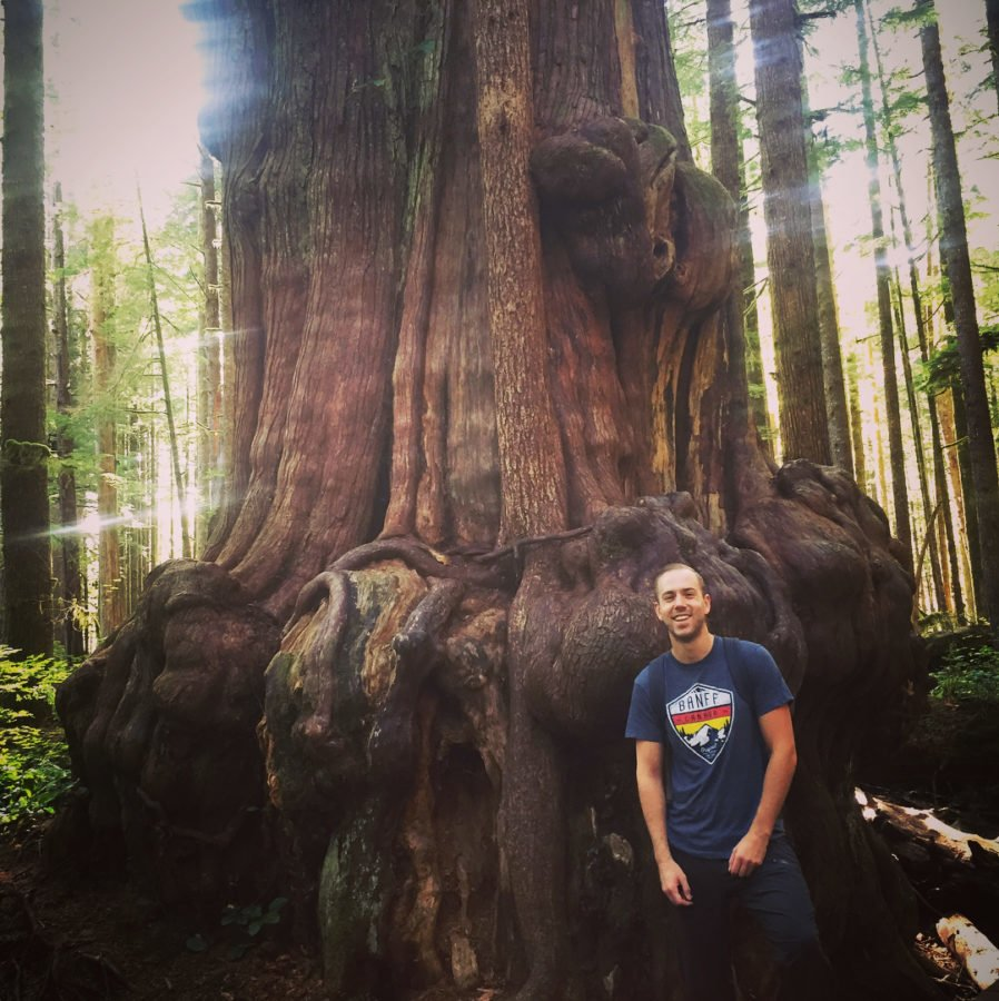 Scott standing in a grey tshirt and jeans at the base of a broad tree trunk covered in large round bubble-like bumps in the bark.