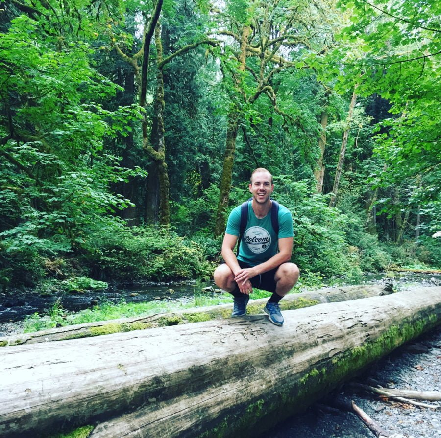 Scott squatting on a large fallen tree, which is lying on rocky ground surrounded by bright green trees. He is in a green tshirt and smiling at the camera.
