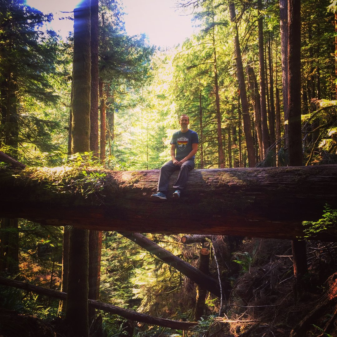 There is a large fallen tree stretching across a shallow valley in a forest, and Scott is sitting in the middle of the fallen tree dangling his feet and smiling. He's wearing jeans and a green tshirt and smiling.