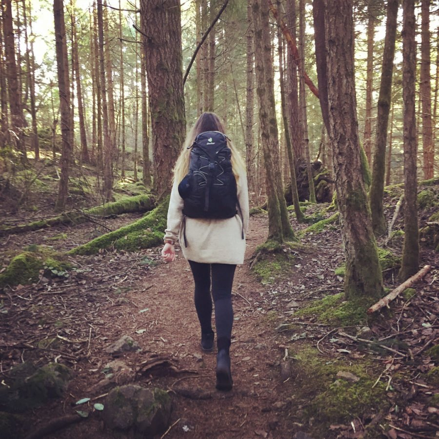 A woman is walking away from the camera with a brown coat and black backpack. She is walking along a path through a forest.