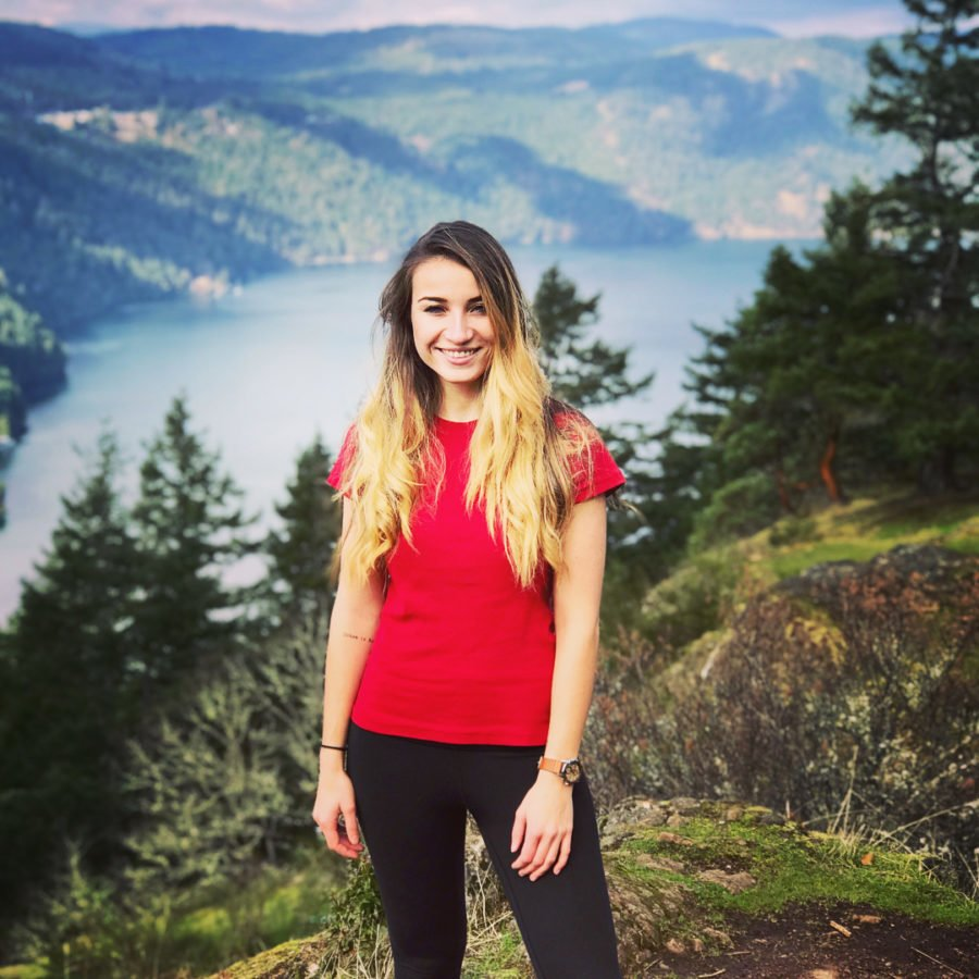 A woman in a red tshirt and black leggings standing infront of a view of evergreen trees and mountains with a body of water down below. It looks sunny. She is smiling.