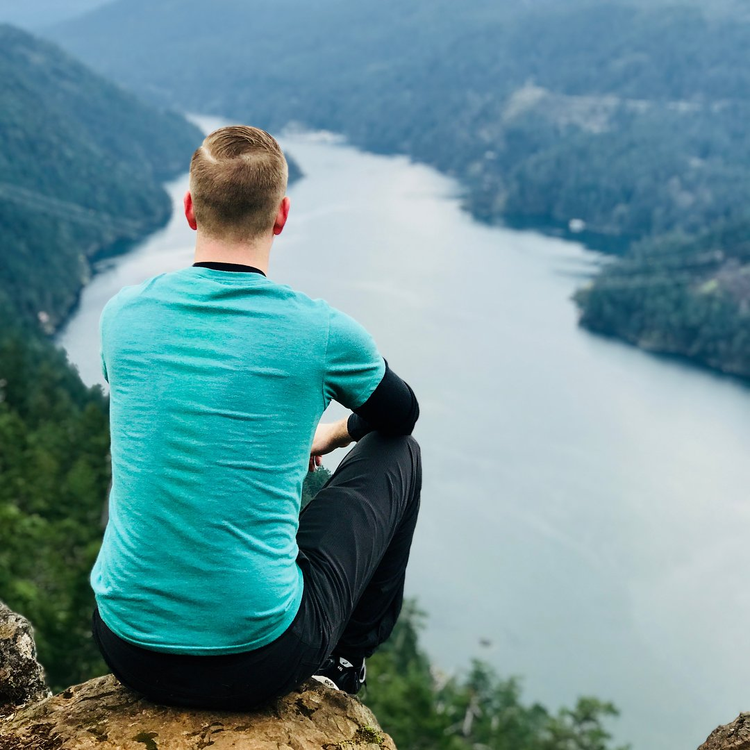 A man in a turquoise tshirt with black sleeves and jeans facing away from the camera and sitting looking out over a long body of water with evergreen trees on either side.