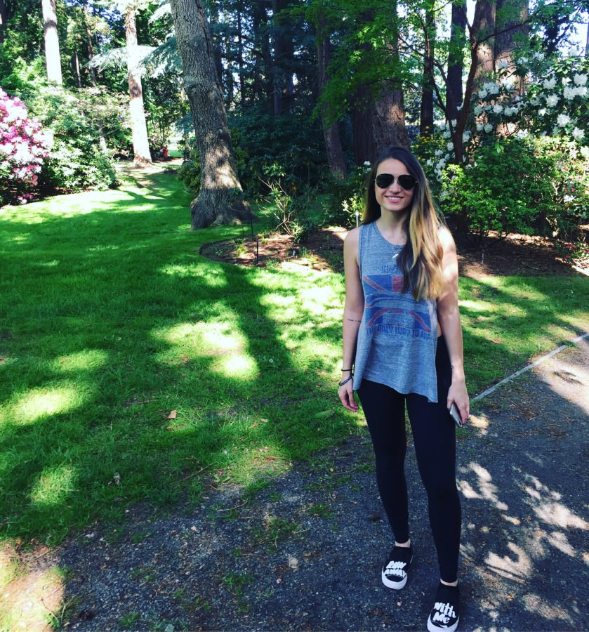 A woman in dark pants and a blue tank top standing on a gravel path in front of a green, sun dappled patch of grass with leafy trees behind her. She has sunglasses on.