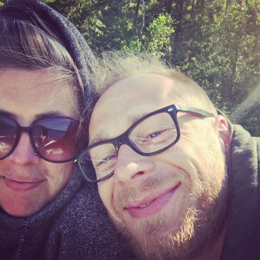 A woman to the left has a grey hood pulled up and sunglasses on with a man in black glasses with a ginger beard leaning on her shoulder. Both are smiling and looking a bit chilly.