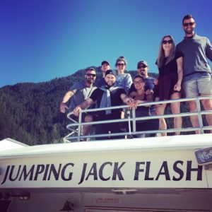 "A group of 8 people in summer clothes standing on a white boat that says ""Jumping Jack Flash"" on the side. Behind them there is a mountain covered in green trees and a blue sky. All are smiling down at the camera."