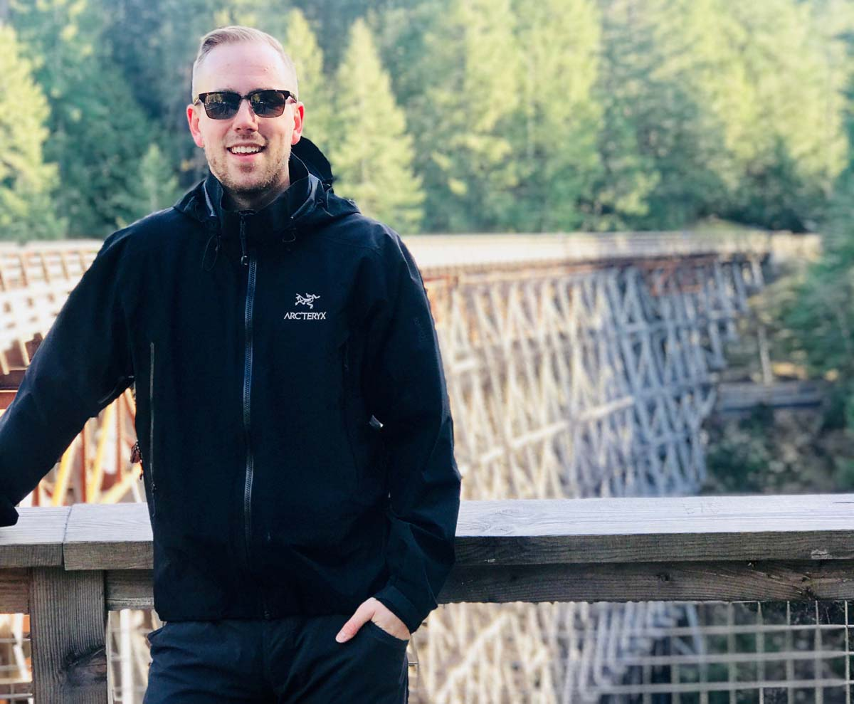 Physiotherapist, Scott in a black jacket, pants, and sunglasses standing in front of a wooden and metal mesh railing with a long wooden railroad bridge spanning into the distance behind him and a forest in the background.