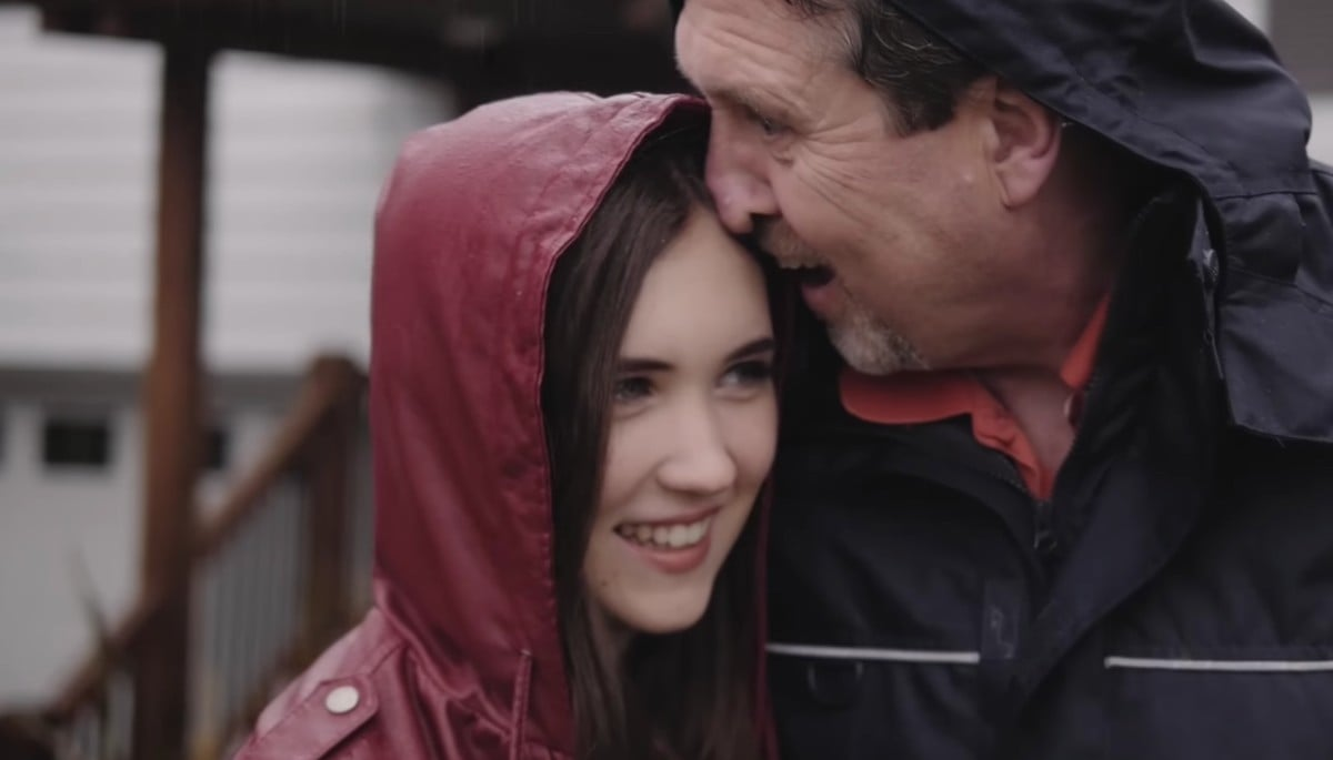 A father (right) and daughter (left) with their heads together smiling widely in the rain.