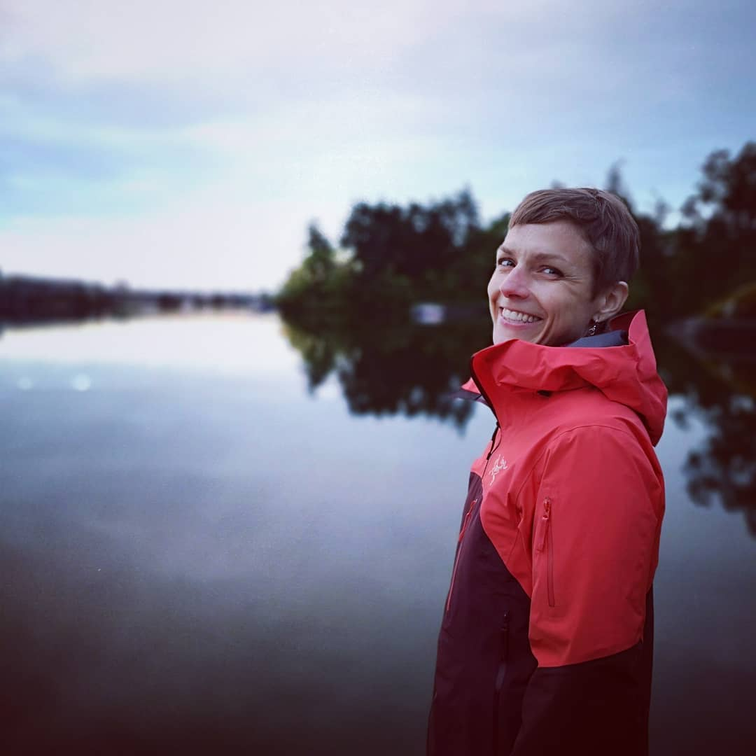 A female presenting person looks over her left shoulder to smile at the camera. The Gorge waterway and shore are behind her.
