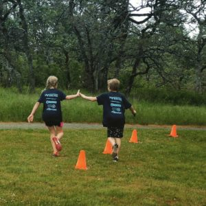 A young athlete gives a sibling a high five at the Westshore Youth Triathlon.