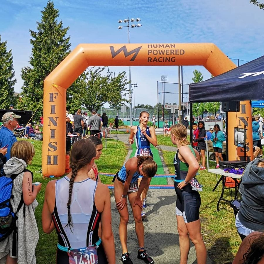 A group of athletes in triathlon bodysuits standing and stretch in front of an inflated orange finish line.