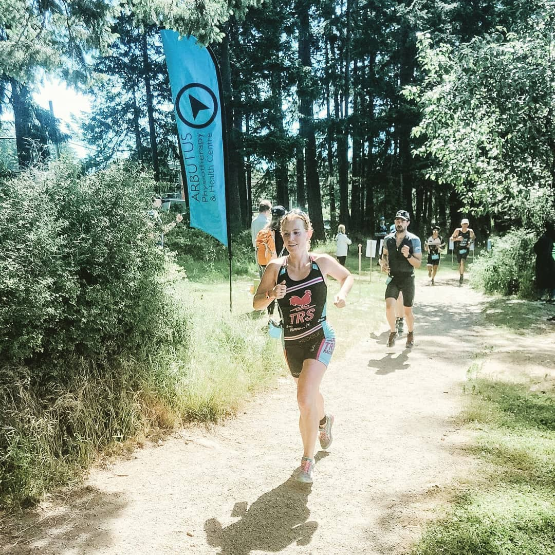 Sophia running along a wooded path in a red and black triathlon suit with a blue Arbutus Physio flag behind her.