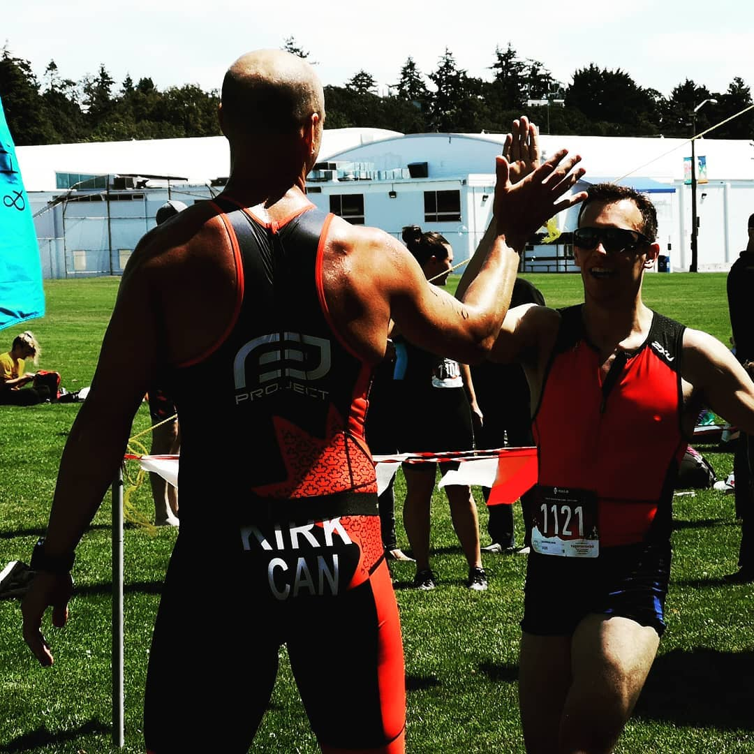 Two people giving each other a high-five in red and black triathlon body suits.