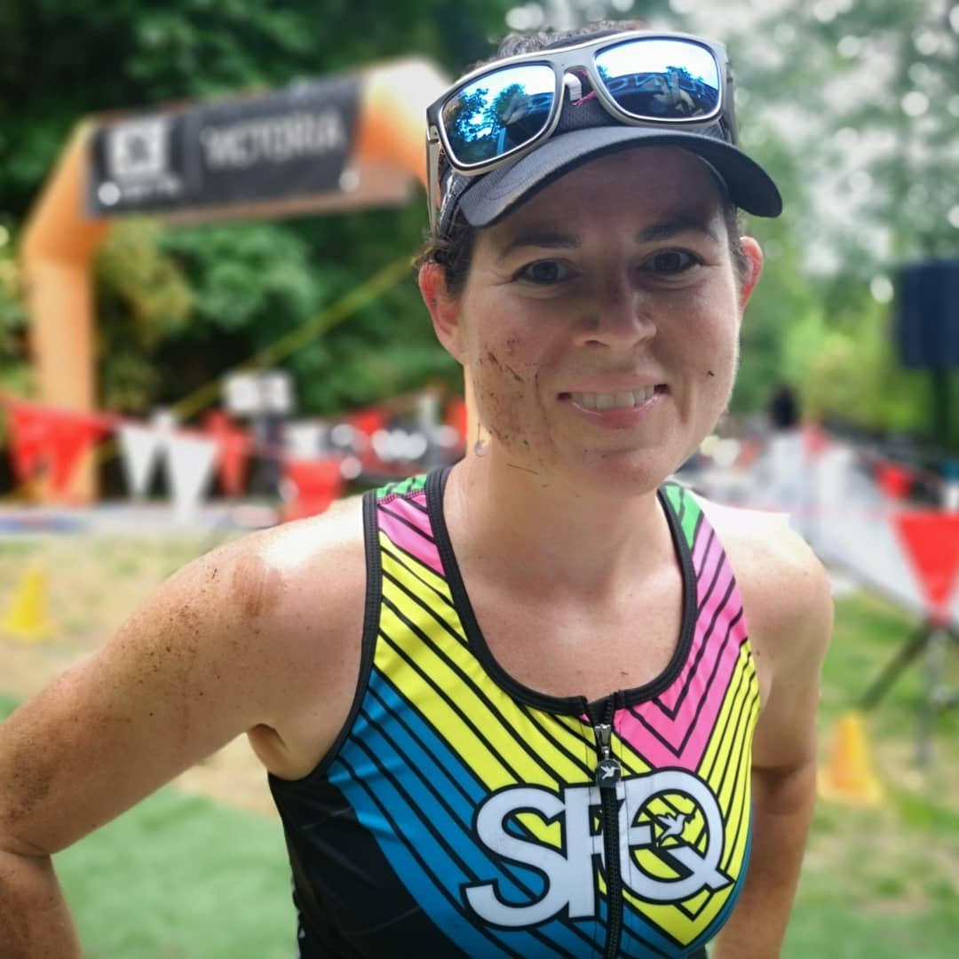 A femme person in a yellow, pink, blue, and black tank top with cap and sunglasses from the upper torso up. She is smiling and very muddy with an orange inflatable finish line out of focus in the background against trees.