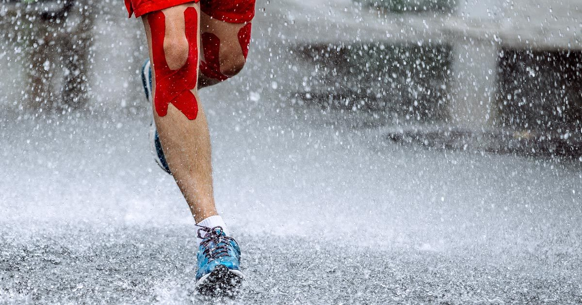 Runner with taped knees out in the rain and water during a race.