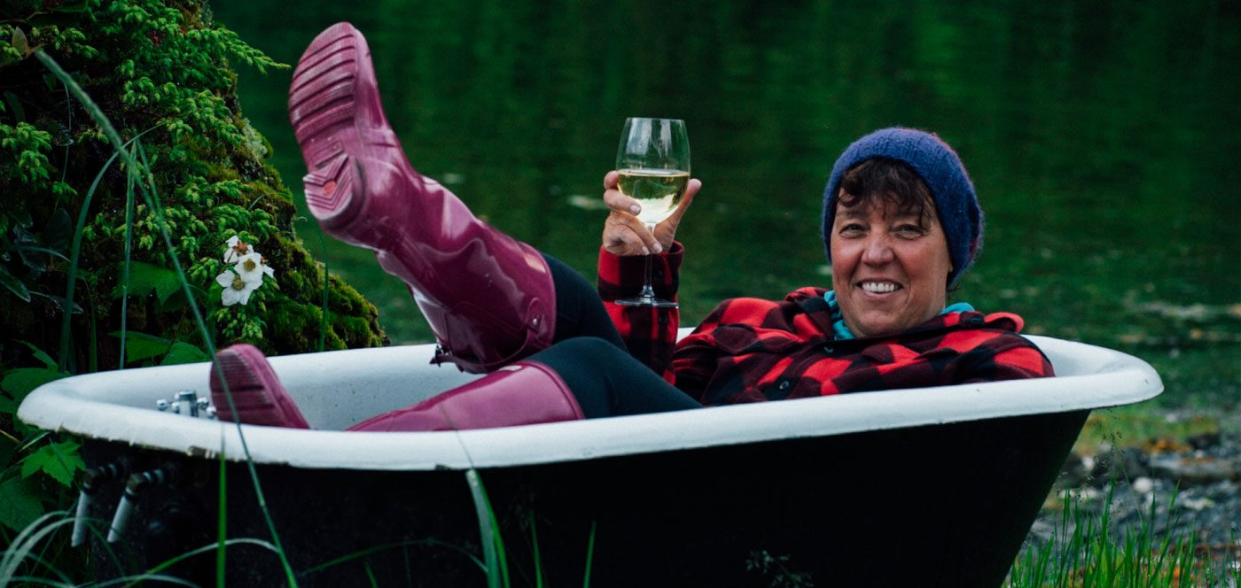 Susan lying back in an outdoor bathtub in a red plaid jackets, pink gumboots, and a glass of wine smiliing widely.