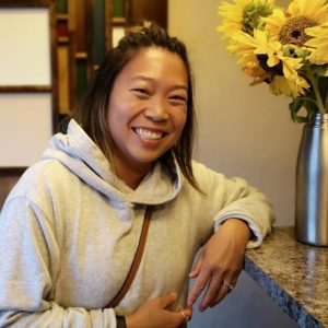 Diana, @dee_jang, leans on our clinic counter beside our autumn sunflowers, smiling widely