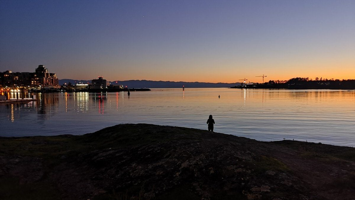 Victoria harbour at twilight, with someone standing in the dark distance.