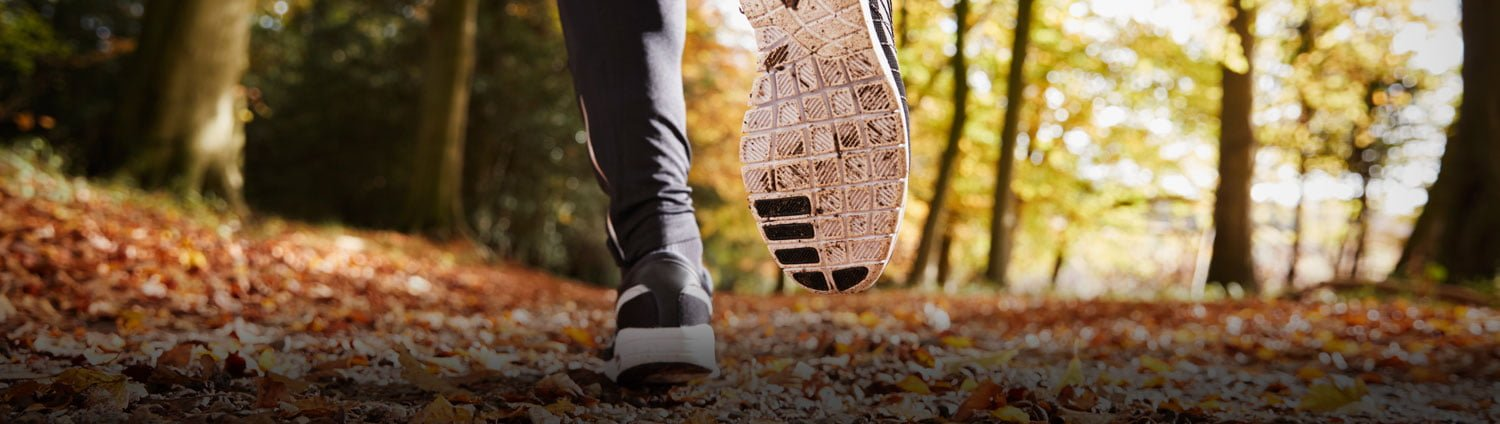 Close up of a runner's shoes as they move through the autumn leaves.
