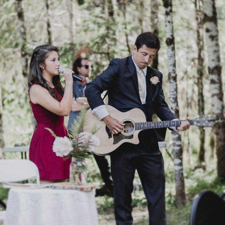 Stephanie Holbrook sings with guitar back up in a forest setting.