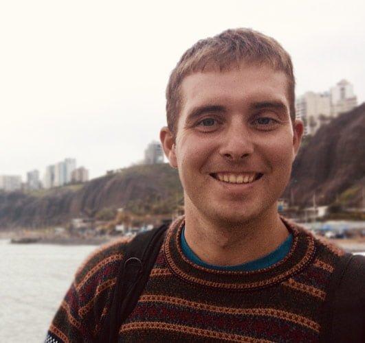 Brandon Warren, Physiotherapist, smiles widely on the beach.