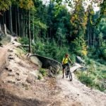 A mountain biker takes a rest near the top of a forest trail.