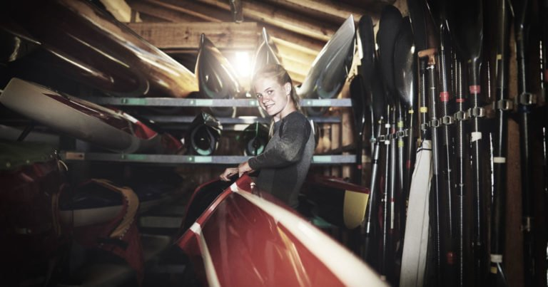 An elite athlete lifts her craft onto a shelf in the rowing shed.