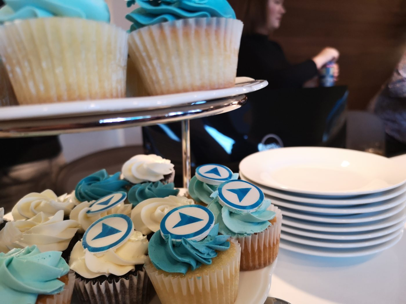 Cupcakes with tiny logos make people smile at the grand opening.