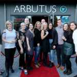 The Arbutus Physiotherapy team stands outside at the Grand Opening on the red carpet.