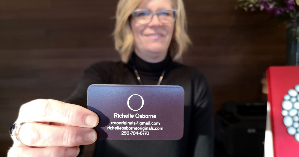 Richelle Osborne holds out her business card.