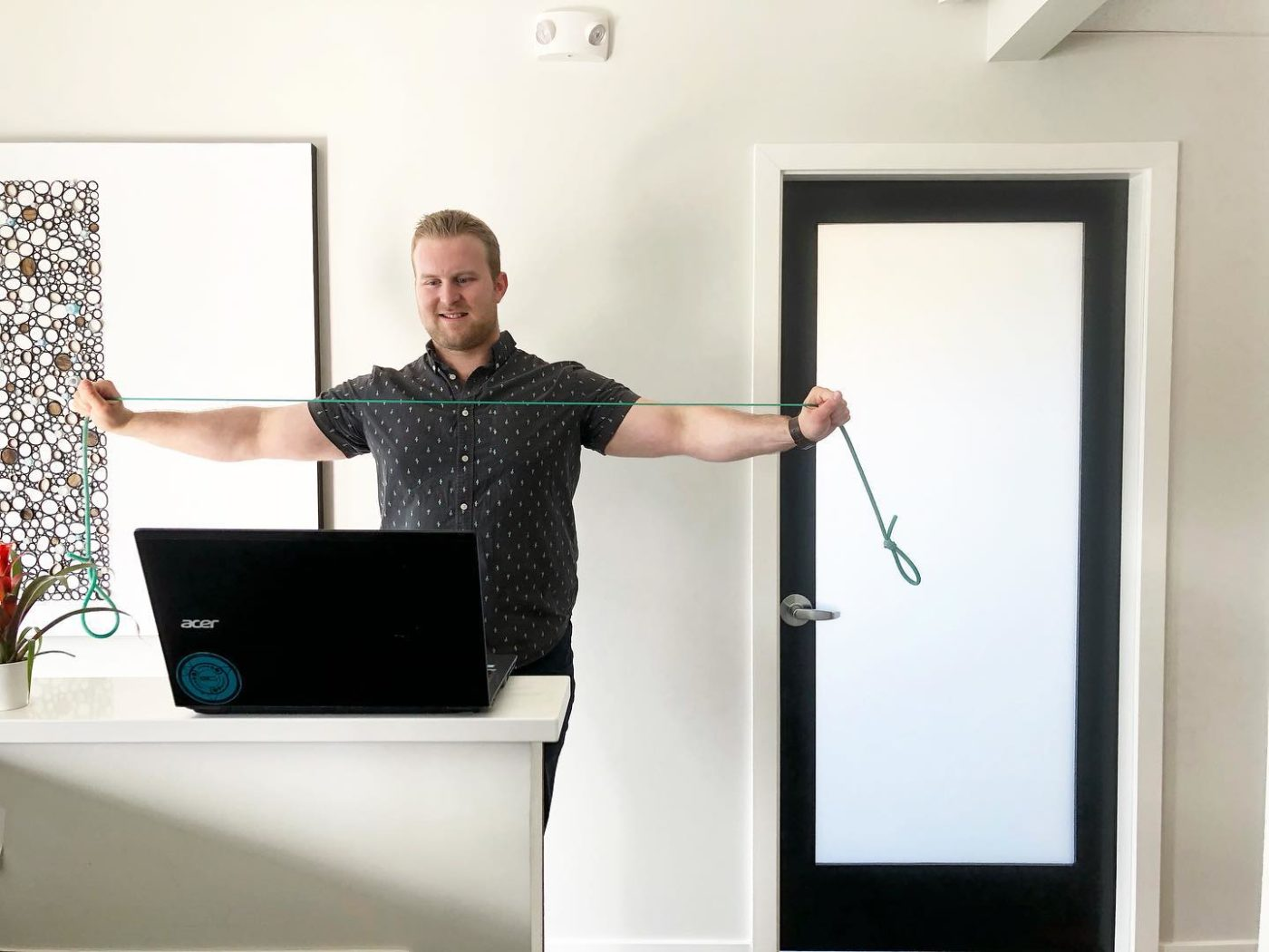 Connor Willis stands in front of the computer video to demonstrate some exercises.