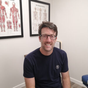 Andrew smiles at the camera in a navy blue tshirt with brown, rectangular frame glasses. He is sitting in front of two diagrammatic images: one of the muscular composition of the body, and one of the human skeleton.