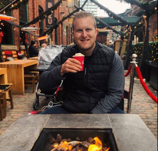 Connor sits across a table with a fireplace in the centre outdoors holding a foamy coffee and smiling.