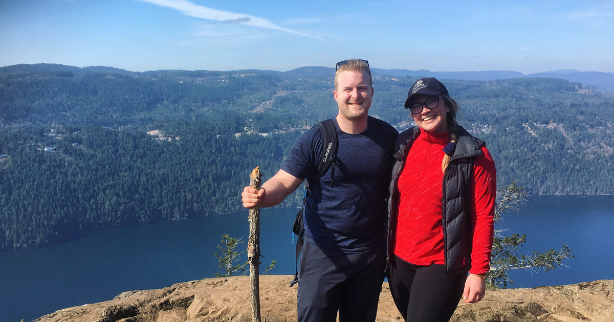 Connor and his partner stand in hiking clothes with trees and water behind them from a high rocky view point. Both are smiling widely.