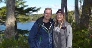 Connor and his partner stand in hiking clothes with trees and water behind them. Both are smiling widely.