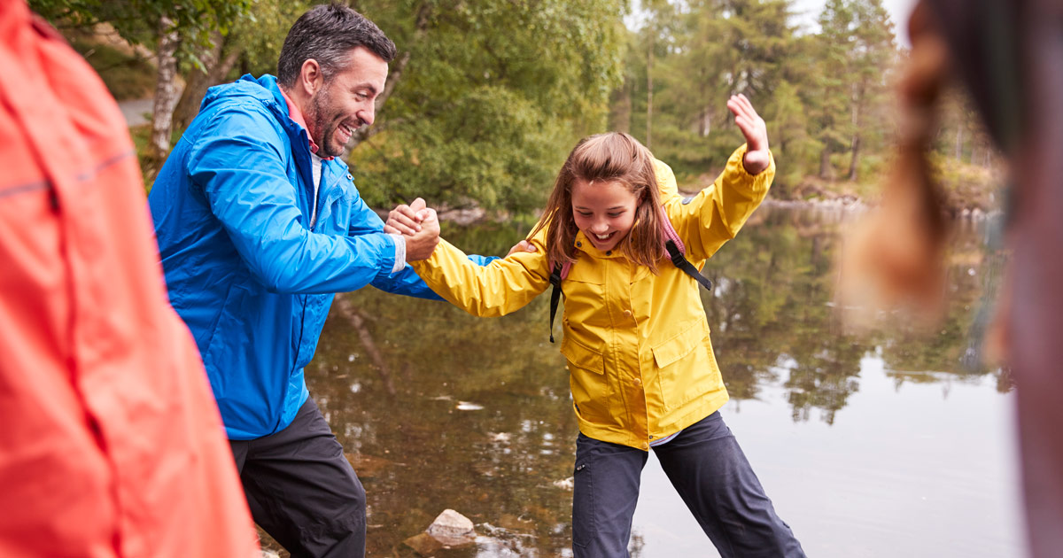 A father reaches out to help his daughter balance on a hike by water.