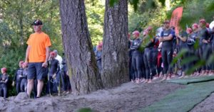 Rob stands to the left on a hill in an orange tshirt at the edge of a forest with a crowd of athletes in wetsuits behind him.