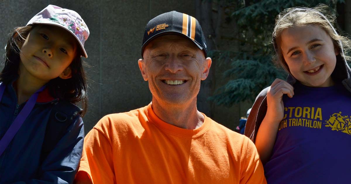 Rob wears an orange t-shirt and smiles widely with two young athletes on either side of him and a forest in the background.