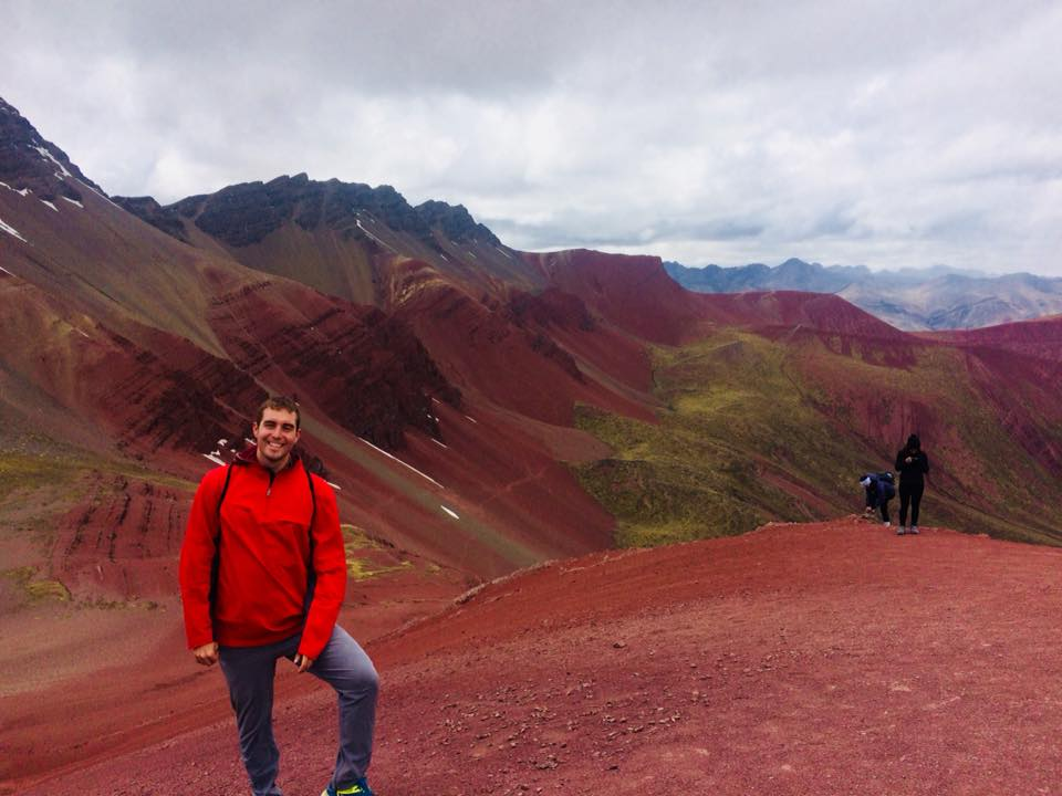 Brandon stands on the left in a red jacket and sweat pants smiling against a receding mountain range of red soil.