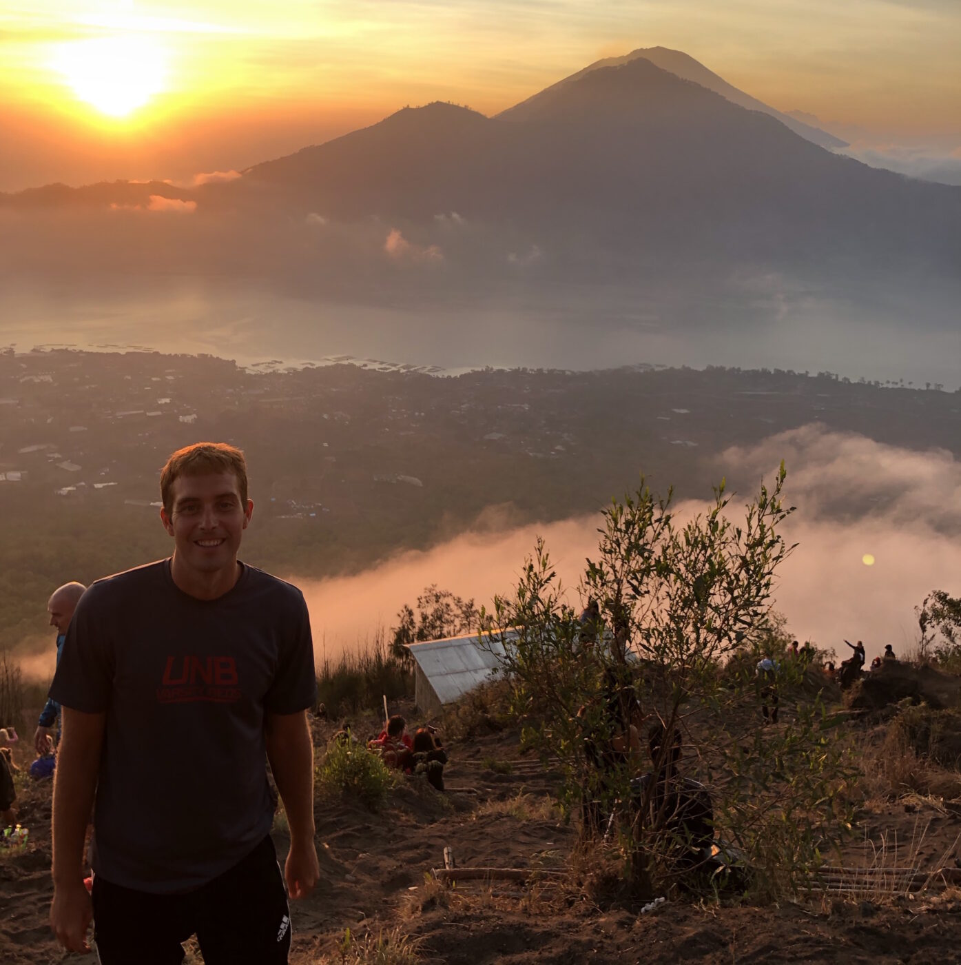 Brandon stands in the bottom left in a grey tshirt smiling against a beautiful sunset with mountains, mist, and a sandy grassy landscape.