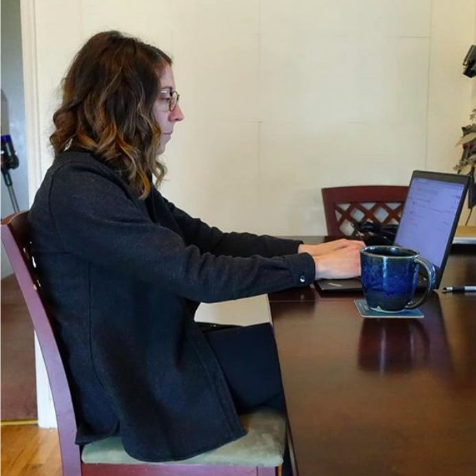Ashley sits slouched at a kitchen chair reaching forward to work on a laptop which sits on a dining room table.