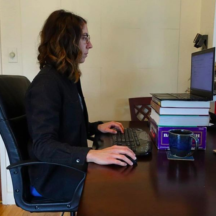 Ashley sits straight on an office chair working on a wireless keyboard connected to a laptop. Her elbows are comfortably at her side, and the laptop is propped up on a stack of books.