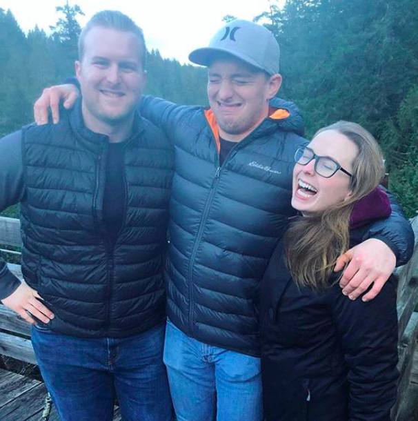 Connor and two friends stand making smiling, goofy faces with their arms around each other in the woods.