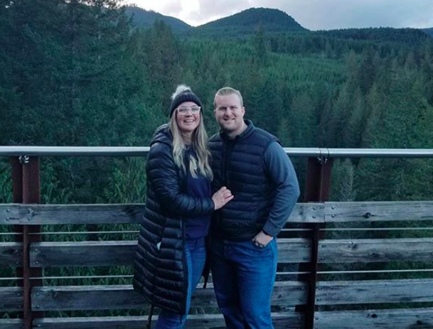 Connor and his partner stand against a wooden railing with a lush backdrop of trees and mountains behind them against a grey sky. They are both smiling and wearing hiking clothes.