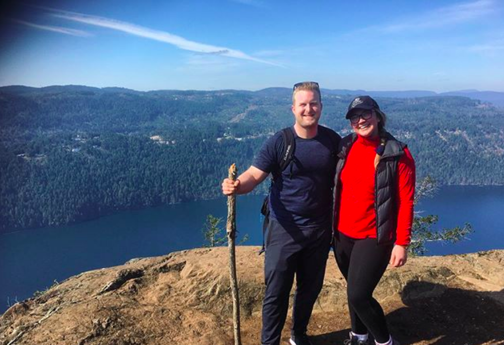 Connor and his partner stand together at a view point with water down in the distance behind them. They are on dry rocky ground and wearing hiking clothes under a blue sky.