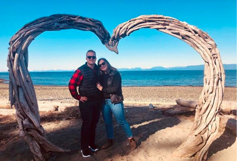 Connor stands with his partner under a driftwood sculpture shaped like a heart. They are on the beach with the ocean behind them on a sunny day.
