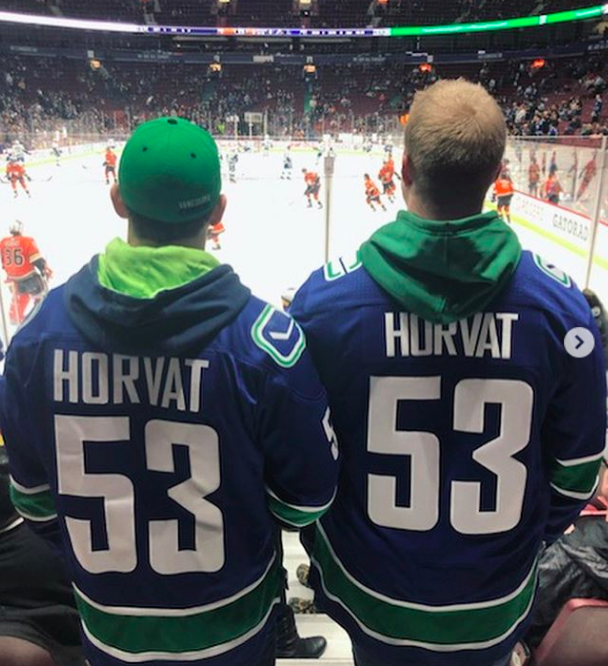 """Connor and another person stand shoulder to shoulder wearing matching Canuck Jerseys with a hokey game happening on the ice in the stadium behind them. They face the ice rink with their back to the camera showing off their matching """"Horvat"""" jerseys."""