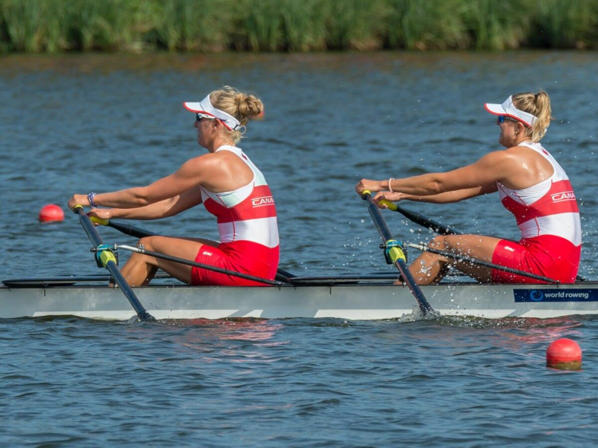 Two women wearing red and white uniforms rigorously rowing on calm water with tall grass in the background.
