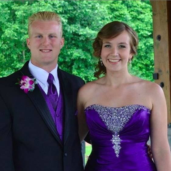 Connor stands next to his partner outside. Both are smiling in formal wear. He is wearing a black suit and a purple tie. The tie matches his partners formal gown, which also has rhinestones along the bust.